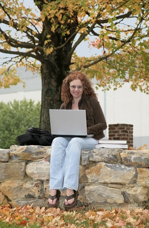 one twenties redhead studying on a laptop outdoors in fall Banque d'images
