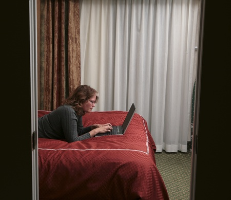 woman lying on bed reading her pc laptop Banque d'images