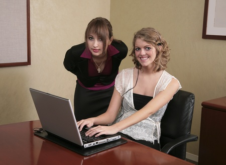 two attractive business women working on a laptop computer to solve a problem