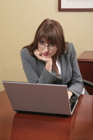 sexy twenties business woman working in an office on a laptop pc