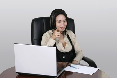 pretty brunette office worker with a laptop at her desk