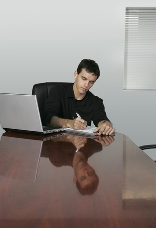 twenties guy writing at a conference table in an office