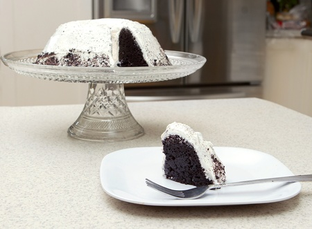 one slice removed from a chocolate cake with white vanilla frosting