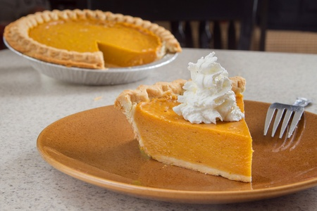 one slice of pumpkin  pie removed from the whole and ready to eat Stock Photo - 12749864