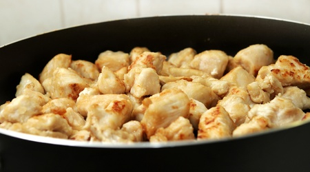 several pieces of chopped up chicken breast browned in a frying pan Banque d'images
