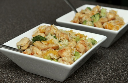 close up bowl of ginger orange chicken with broccoli and soy sauce Banque d'images