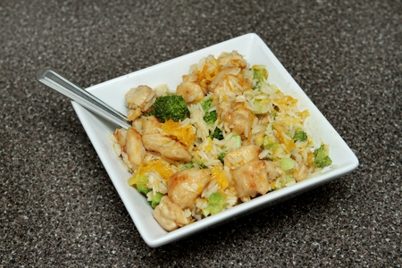 close up bowl of ginger orange chicken with broccoli and soy sauce photo
