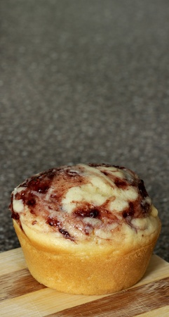white chocolate and raspberry flavored muffin on a cutting board