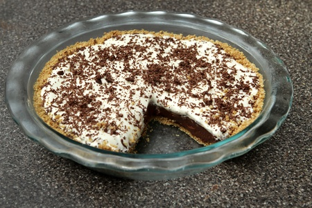 one slice removed from a chocolate cream pie in a glass plate Banque d'images