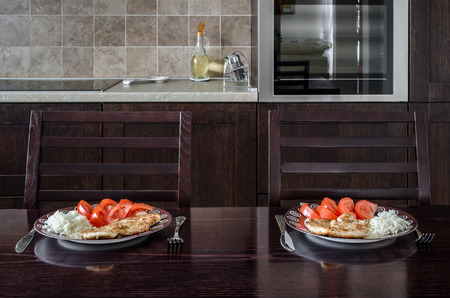 interrior: Dinner at the kitchen. Steak, rice and tomatoes Stock Photo