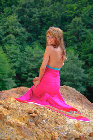 Sexy young girl smiling dressed in pink dress and standing on a rock. photo