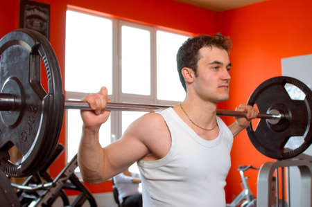 Young man lifting weights in a red room at the gym photo