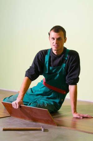 Man carpenter laying a floor with laminated flooring boards while looking into camera. photo