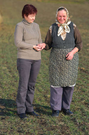 Younger woman hold hand of an elderly countryside woman while help her walk. photo