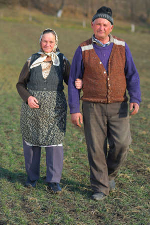 Elderly couple on a countryside field walking together confused. photo