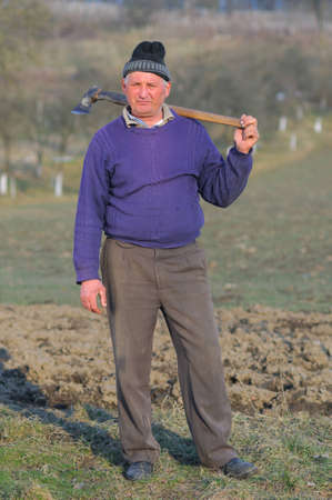 Posing woodcutter near the forest with a hatchet on his shoulder. photo