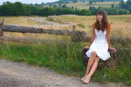 Sexy young girl in white dress, standing on the side of the road on a luggage and waiting for a ride. photo