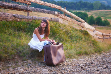 Sexy young girl in white dress, standing on the side of the country road on a luggage and waiting for a ride. photo