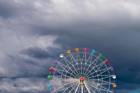 Colorful ferris wheel with black clouds background. Panoramic wheel illuminated by the sun during thunderstorms