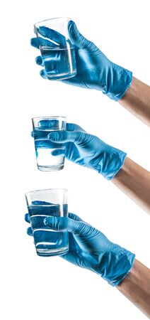 Some hands with blue latex glove holding a glass water Foto de archivo