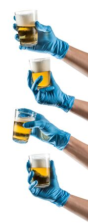 Some hands with blue latex glove holding a glass beer