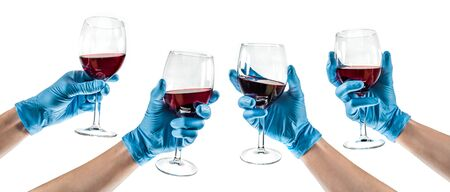 Some hands with blue latex glove holding a glass wine Foto de archivo