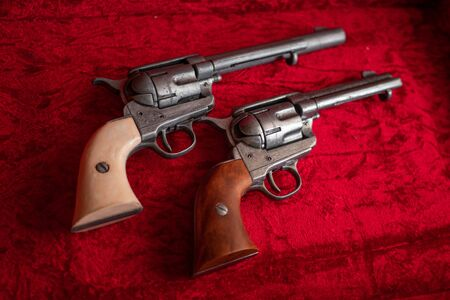 Two old wild west revolvers with brown and white wood grips over red velvet.