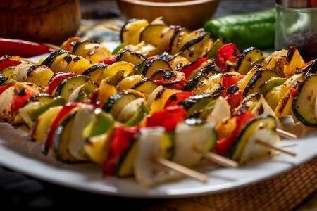 Vegetable skewers in a white plate with some ingredients around