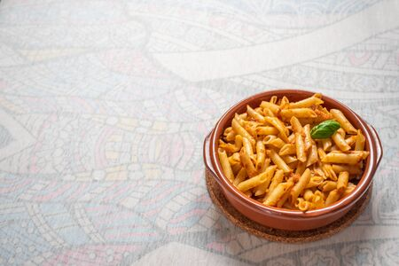 Macaroni with red pesto in a clay pan