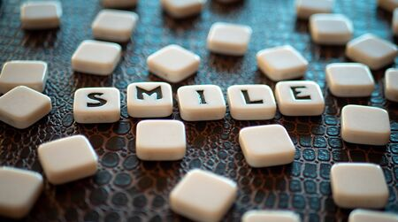 """Crossword game pieces forming the word """"smile"""""""