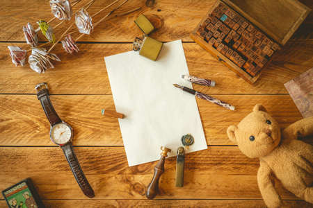 A blank sheet paper to write a letter on a wooden table with some memories