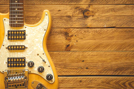 Beautiful vintage electric guitar on a brown wooden table, with copy space.
