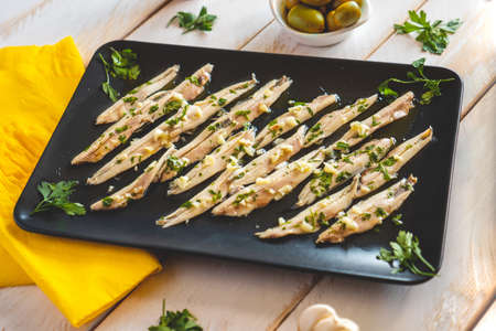 Pickled anchovies in a dark rectangular plate on a white wooden table with others snacks. Typical Spanish food to eat in a bar. Reklamní fotografie