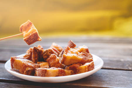 """A toothpick holding a piece of fried pork rinds called """"Torreznos"""" over a small white round fried pork rinds plate on a dark wooden table. Photo with selective focus."""