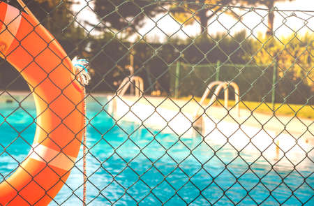 View of a salt water pool from the fence with an orange life float on a sunny summer day. Standard-Bild