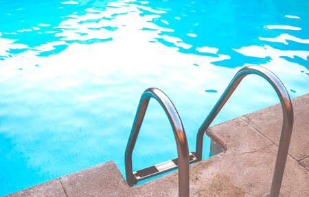 Metal stairs of a salt water pool on a summer day.
