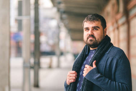 Bearded guy in blue sweater, standing on the street with his hands on his scarf, looking at the camera.