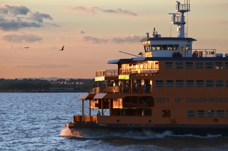 The ferry to Staten Island sails the bay at sunset