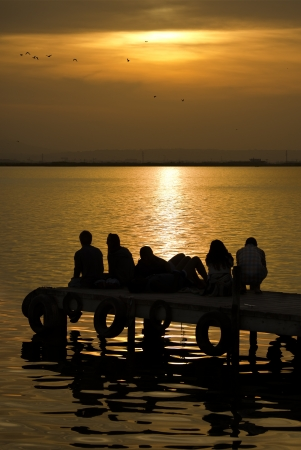 A group of people watch the sunset in the Albufera lake, in Valencia