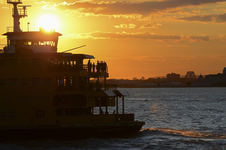 The Dark Silhouette of Staten Island Ferry against the Sun at Sunset.