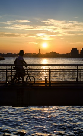 People Walk on a Bridge, Carrying a Bike in the Sunset