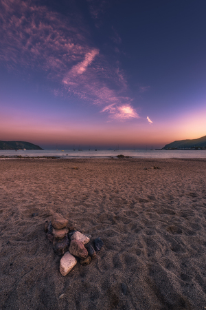 A vertical shot made on a beach of the island Elba in Italy. In the foreground you see some stones lying in the sand. In the background you see the sea. The clouds in the sky are colored in a wonderful red color. Standard-Bild