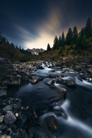 A long exposure taken from a river in the swiss alps at sunset.