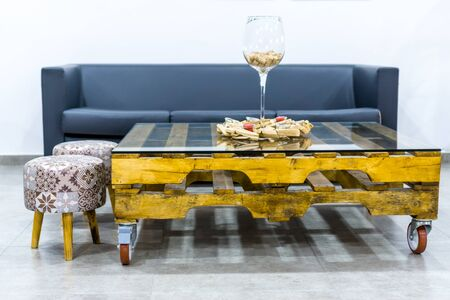 Simple Glass Table with two pallets, two stools, a sofa and a big glass of wine with cork stoppers