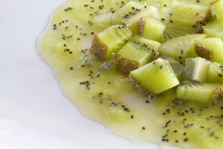 Several cubes of fresh kiwi placed on a white plate over some kiwi juicy Stock Photo - 17599038