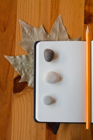 Macro from a notebook with three stones and a leaf on a wood table photo