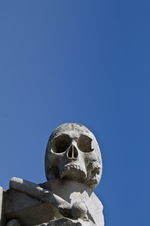 Sculture of a stone skull with blue sky behind photo