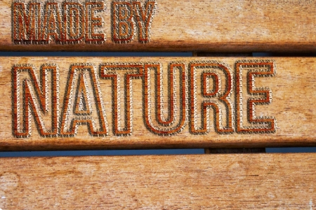 Untreated brown wood with made by nature phrase photo
