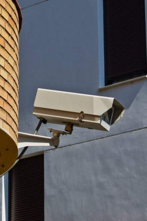 Surveillance camera on a wall of a city photo