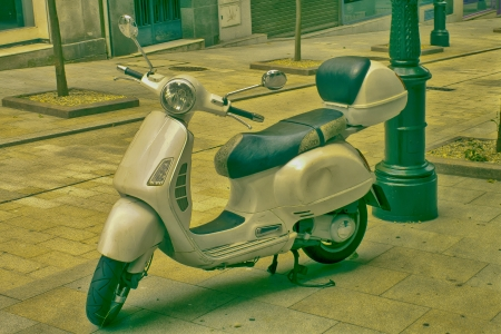 Scooter parked in a typical city street in vintage colours photo